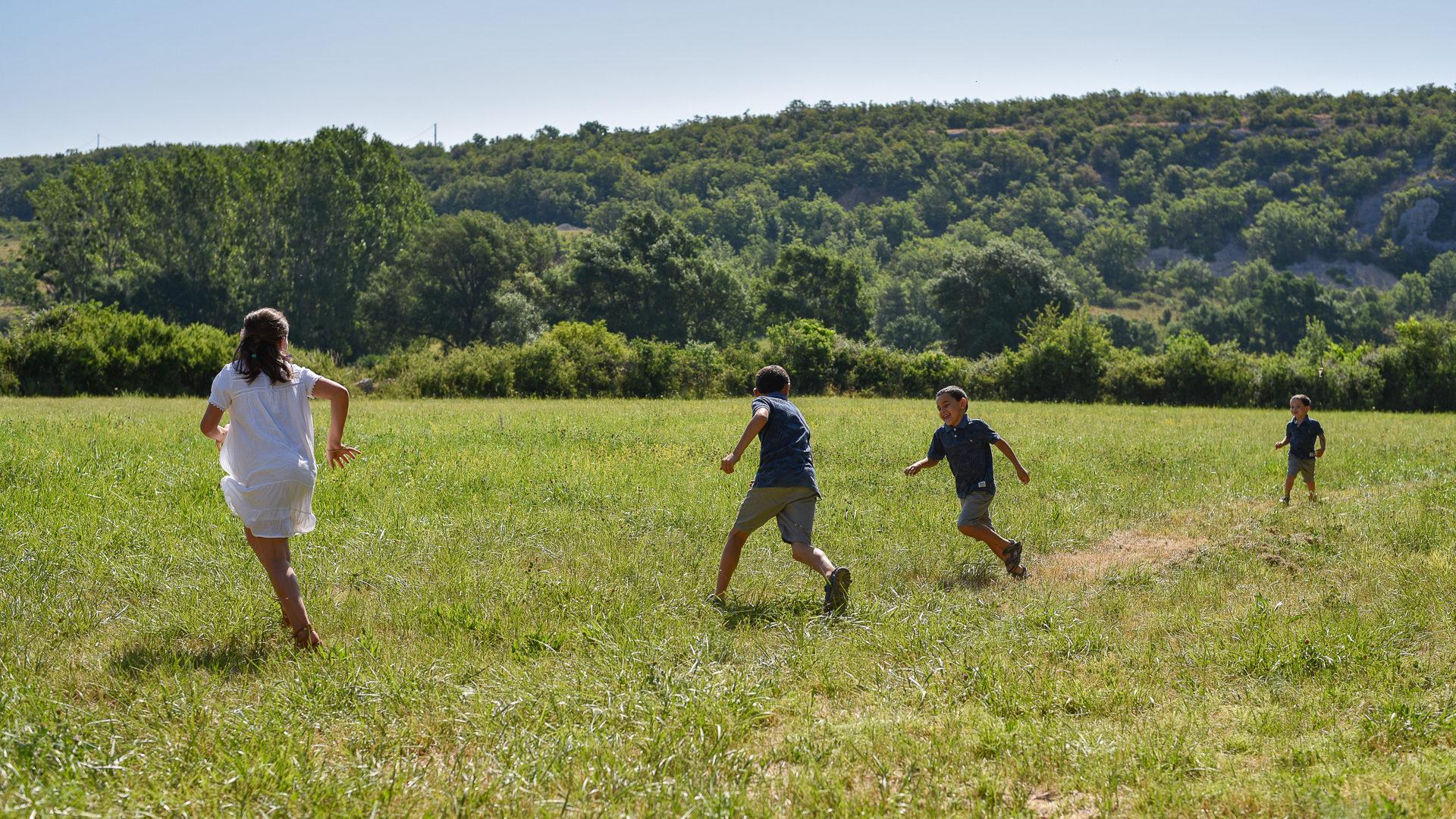 Des enfants courent dans l'écrin de verdure naturelle du Domaine Cassan