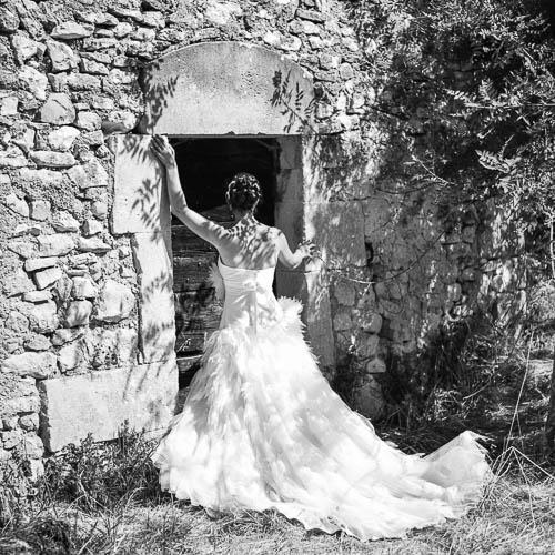 mariée devant un bâtiment en vieille pierres : la bergerie du Domaine Cassan